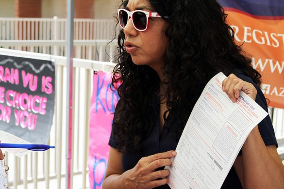 Teresa Martinez, voting rights ambassador for the Arizona Secretary of State, explains the information on a voter registration form to several high school students at a mock election event on April 12, 2016. (Photo by Marianna Hauglie/News21)