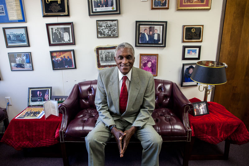 Tuskegee Mayor Johnny Ford sits in front of a wall of photographs in his office. Ford said the wall is a mix of professional and personal mementos. (Photo by Jeffrey Pierre/News21)