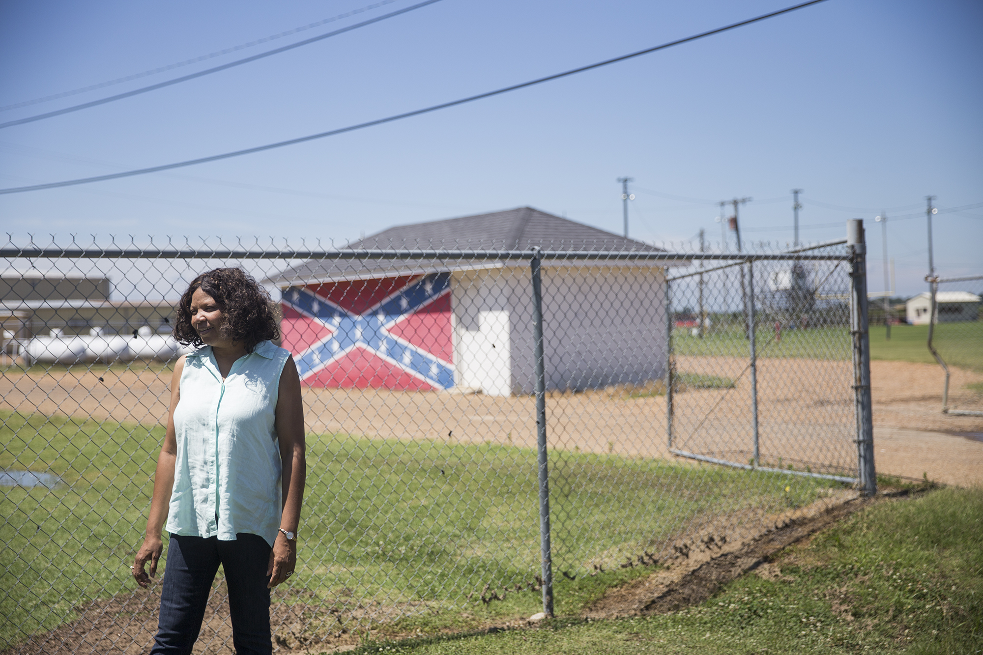 Gloria Dickerson stands in front of a shed at North Sunflower Academy, a private school where many white students enrolled after integration. Today the academy is the town's only high school, but enrolls white students almost exclusively. (Natalie Griffin/News21)