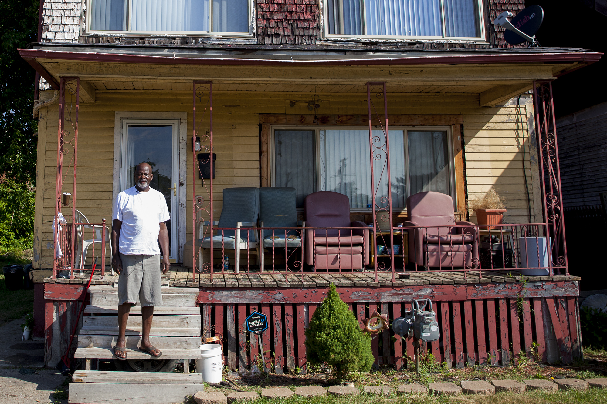 Richard Cooper stands on his front porch in Highland Park, Michigan, across from an empty lot where his elementary school once stood. (Photo by Jeffrey Pierre, audio by Lily Altavena/News21)