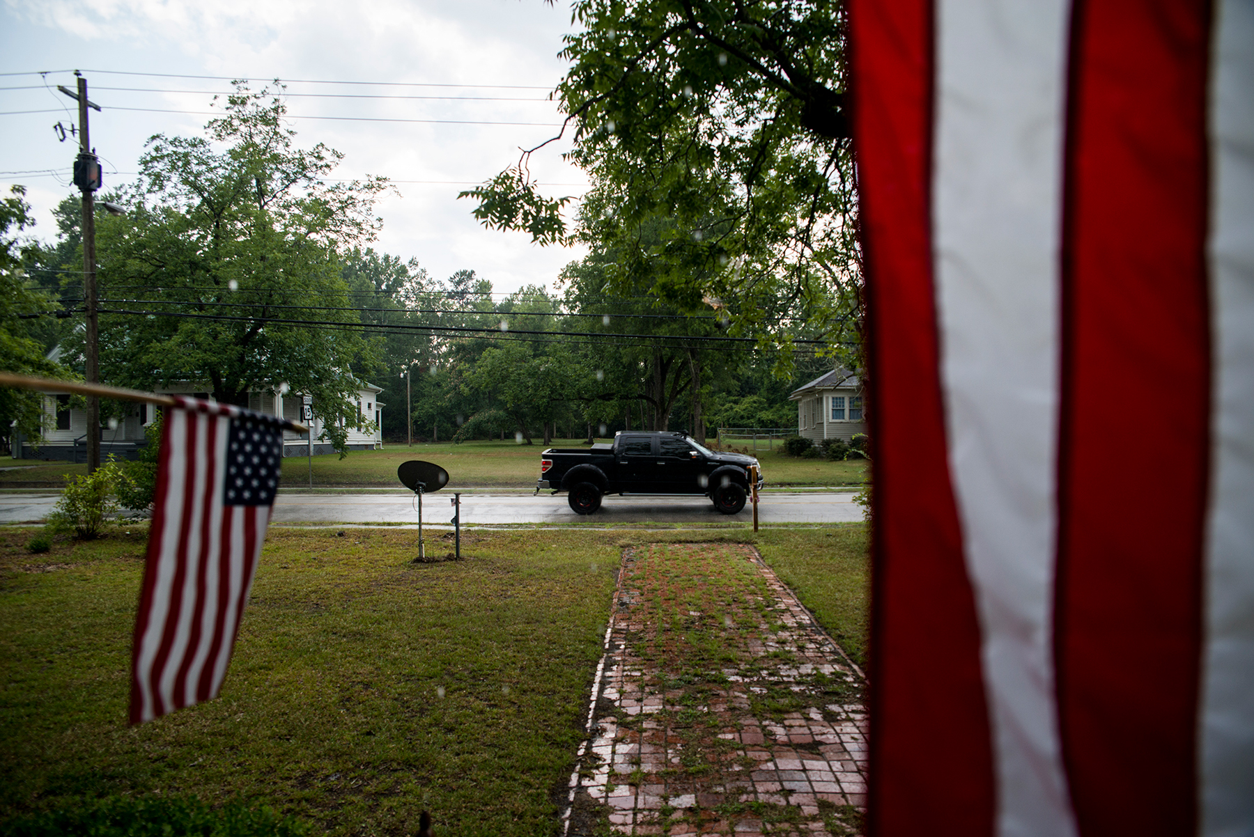 Residents in Sparta, Georgia, display American flags from their front porch on July 3. The Center for American Progress Action Fund gives Georgia low marks for ballot accessibility. (Roman Knertser/News21)