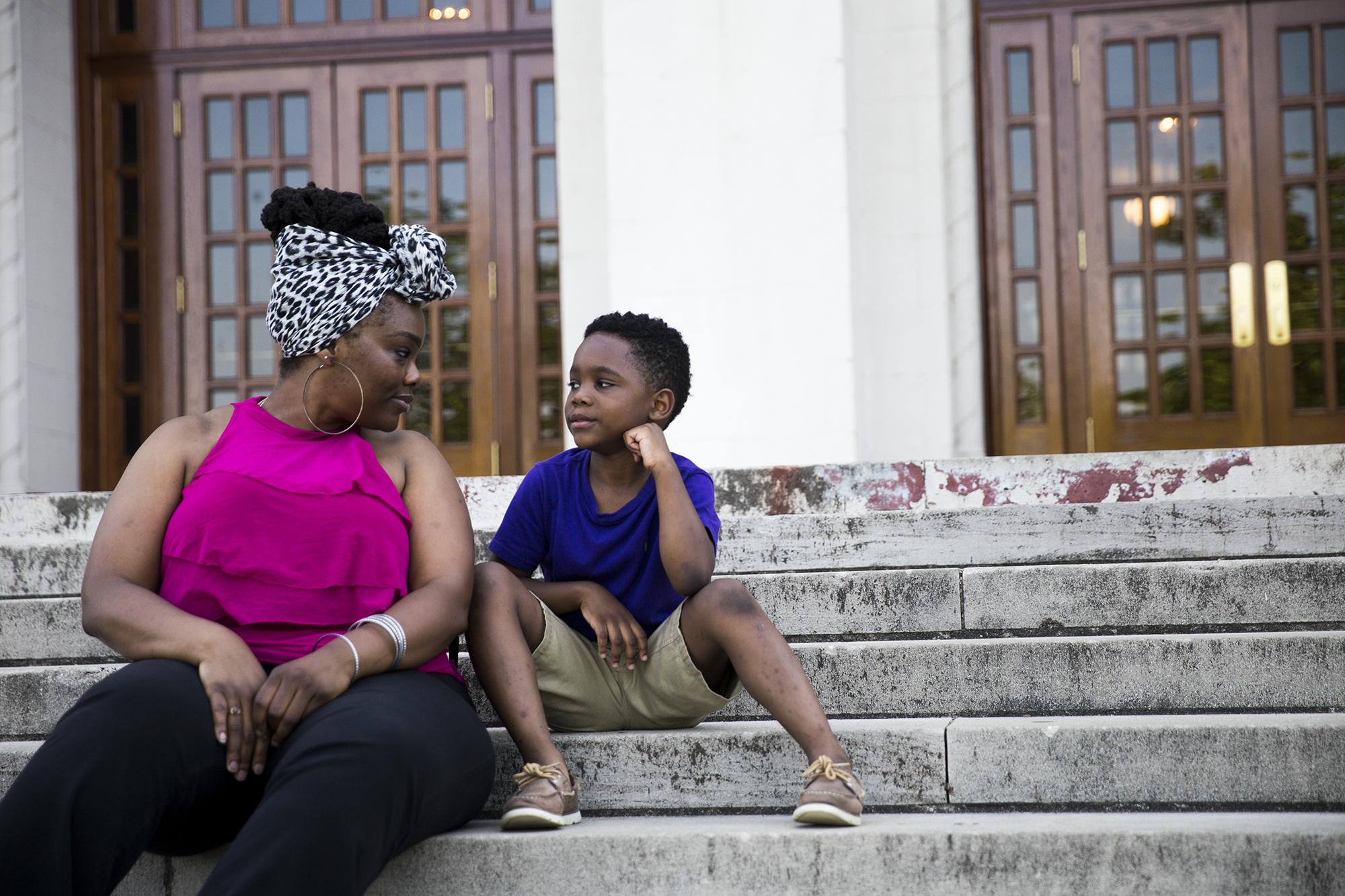 Isis Pettway and her son Caleb sit on the steps of historic Little Rock Central High School, one of the 48 Little Rock schools that Arkansas took control of in 2015. Pettway graduated from the school in 2000 and now sends her 7-year-old son to one of the city's elementary schools. (Natalie Griffin/News21)