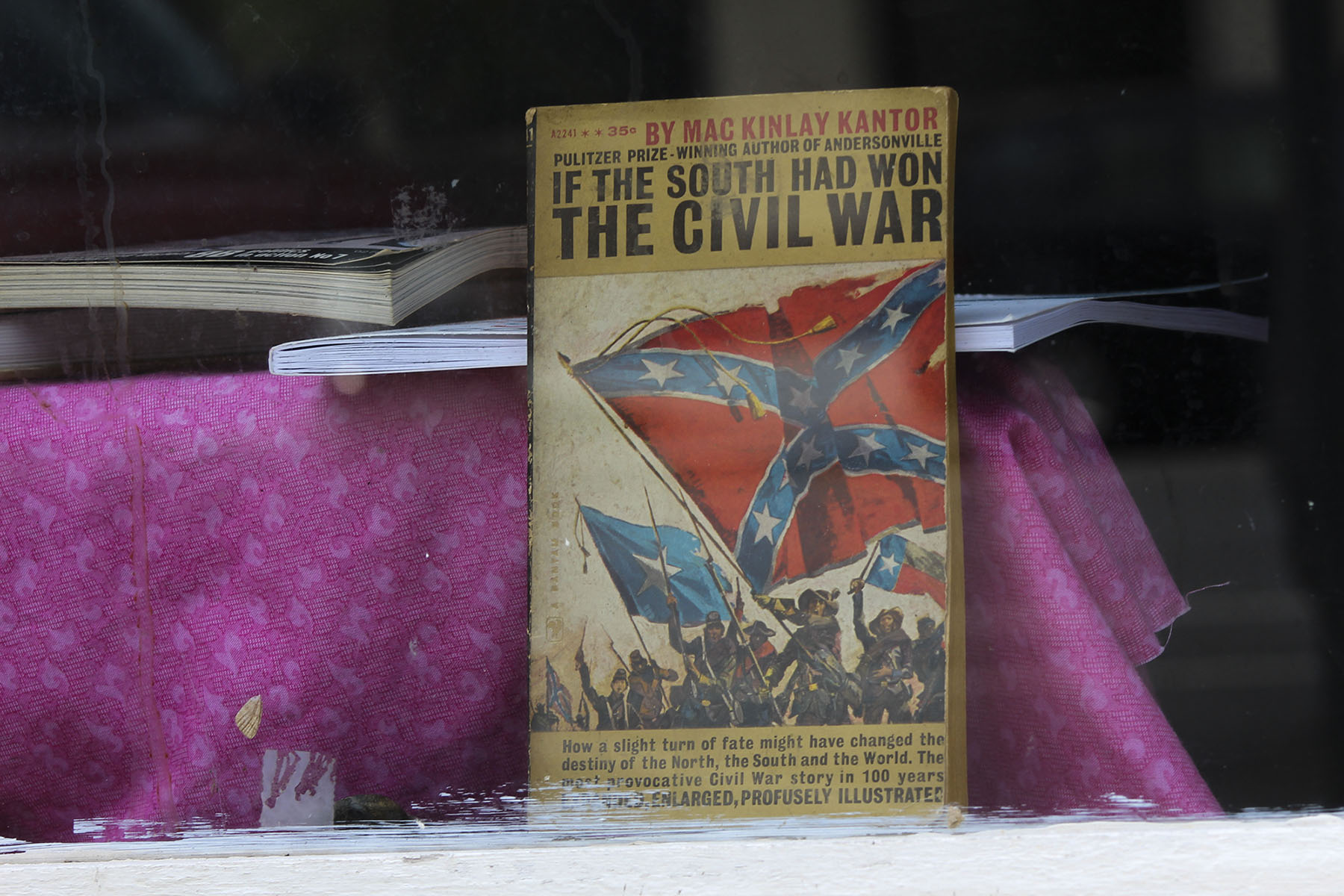 "The book ""If the South Had Won the Civil War"" stands in the window of a bookstore on Cotton Avenue. In the 1800s, cotton was the backbone of Macon's economy, and the city served as an arsenal for the Confederacy. Some say much of Macon's black and white population remains divided today. (Phillip Jackson/News21)"