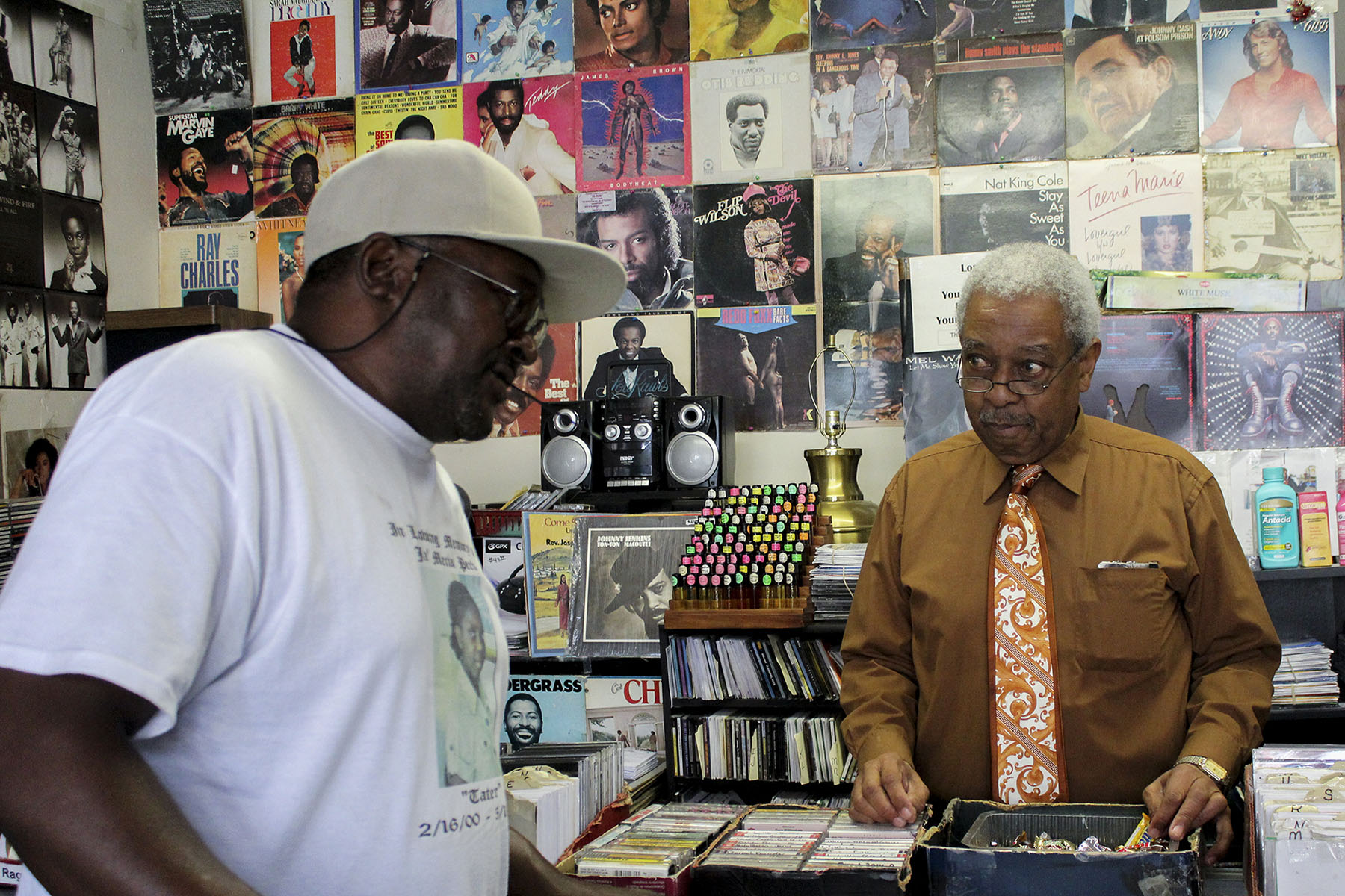 Lafayette Haynes helps a customer at Lafayette Old School Music Store, which he owns. During the civil rights era, Macon was a hub for both black businesses and entertainers, including Little Richard and Otis Redding. Consolidation reduced black influence in the area, Ficklin said. (Phillip Jackson/News21)