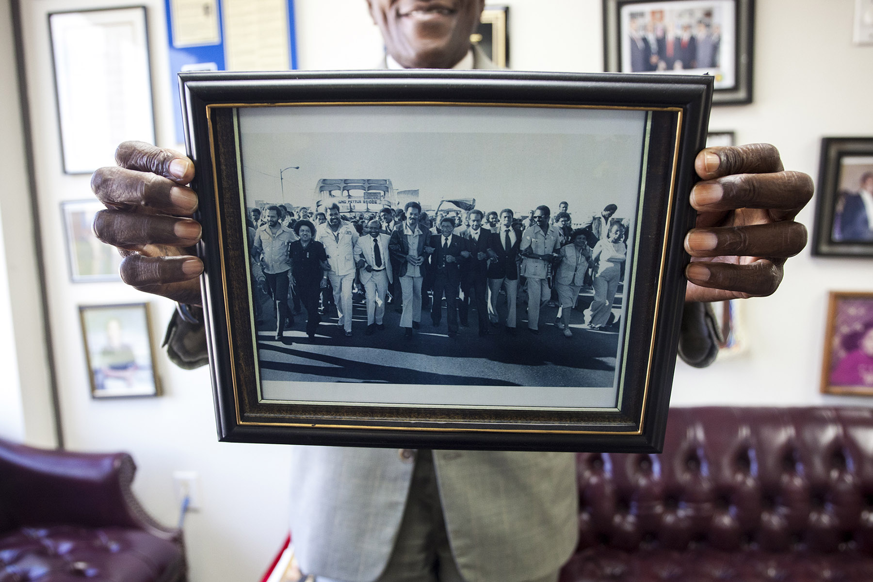 Ford holds up a photo of a commemorative march on the Edmund Pettus Bridge in 2004, but says voter discrimination has not stopped. (Jeffrey Pierre/News21)