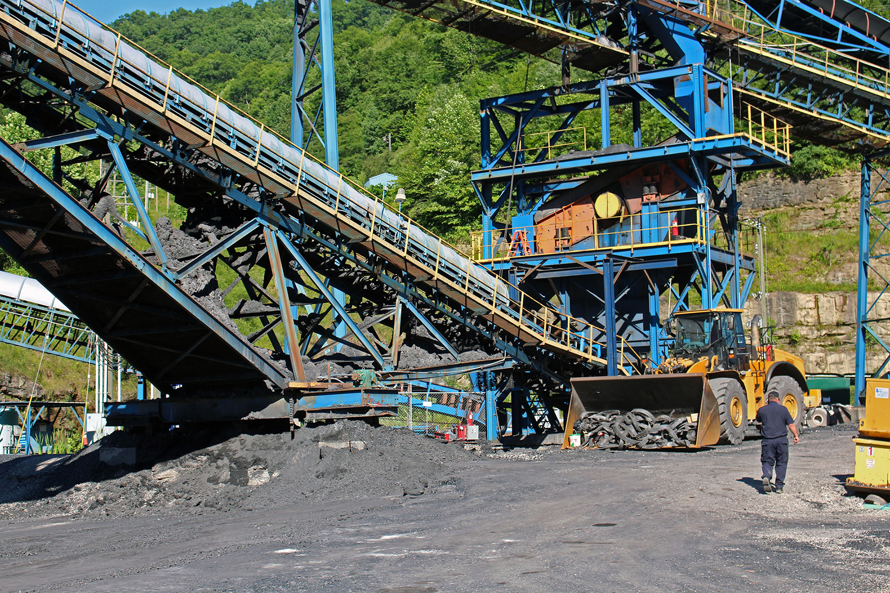 A security guard walks past coal mining equipment at Enterprise Mining Co. in Redfox, Kentucky. The mine went idle in July because of a lack of sales. (Emily Mills/News21)